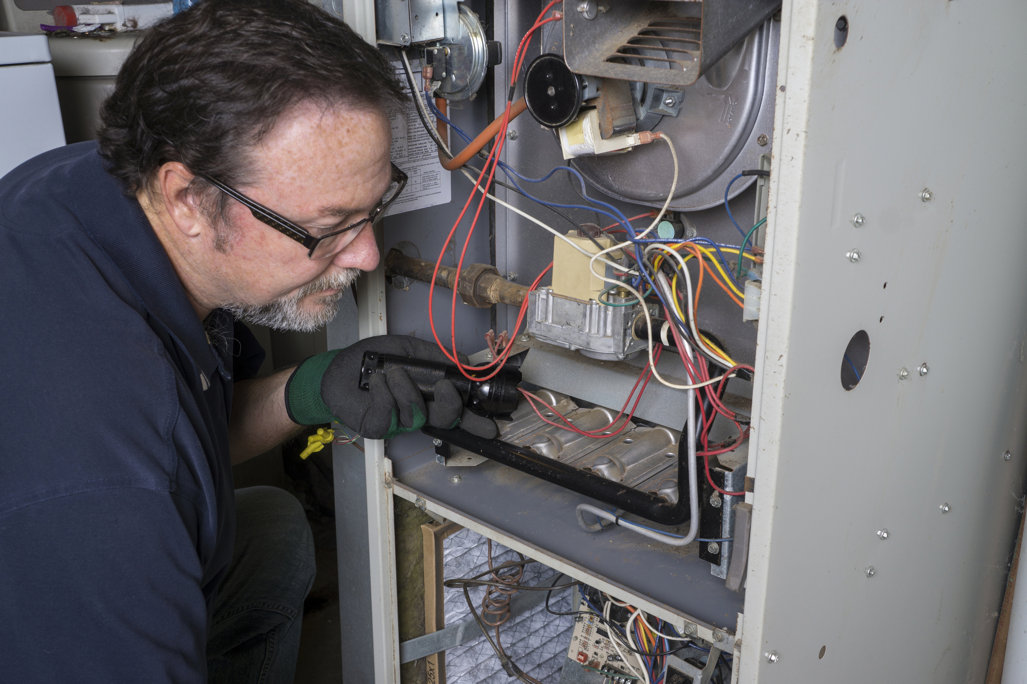 Heating Technician Repairing A Furnace
