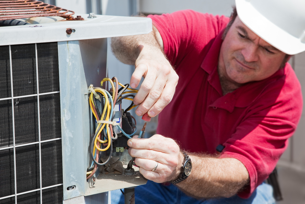 HVAC Repairman Fixing the Compressor in an Air Conditioner